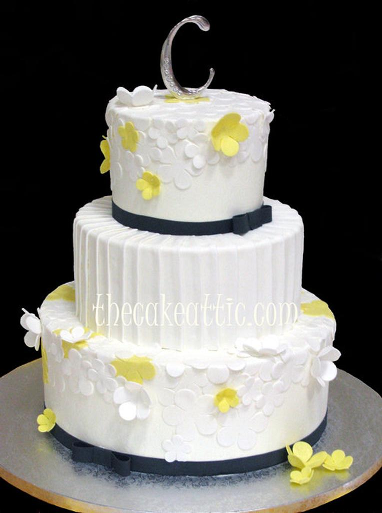 White and yellow flowers with pleated center tier wedding cake by Soraya Avellanet