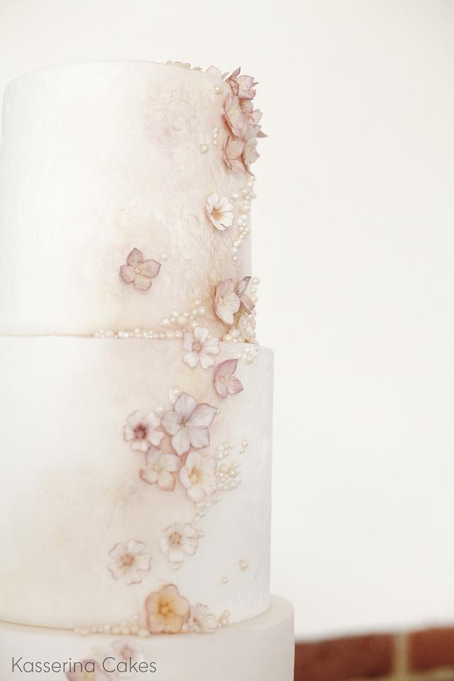 Tall stacked wedding cake with muted blossoms and monogram