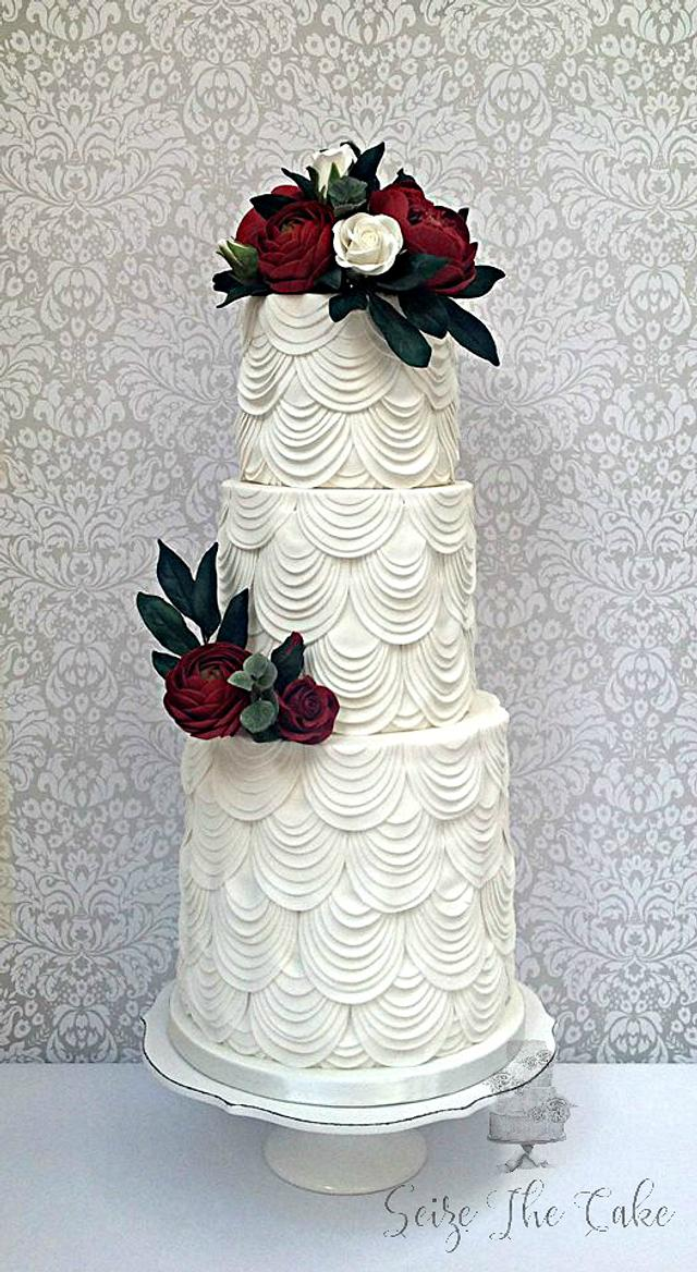 White drapes and red sugar flowers wedding cake