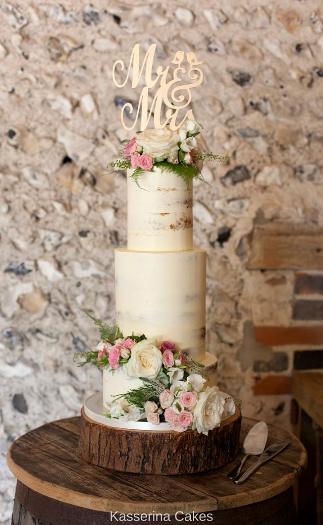 Semi naked tiered cake with fresh flowers and large topper