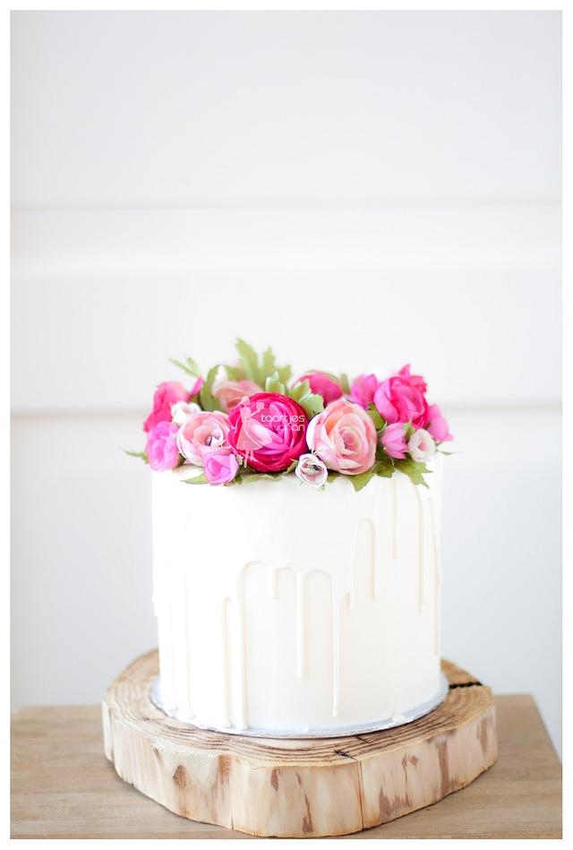 White chocolate dripping cake with handmade flowers