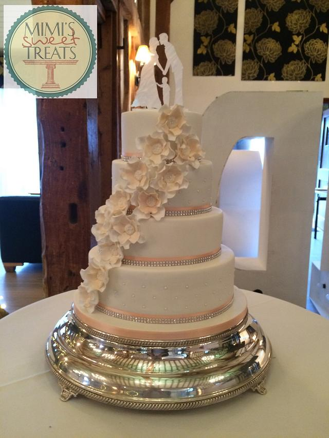 4 tier white wedding cake with peach accents