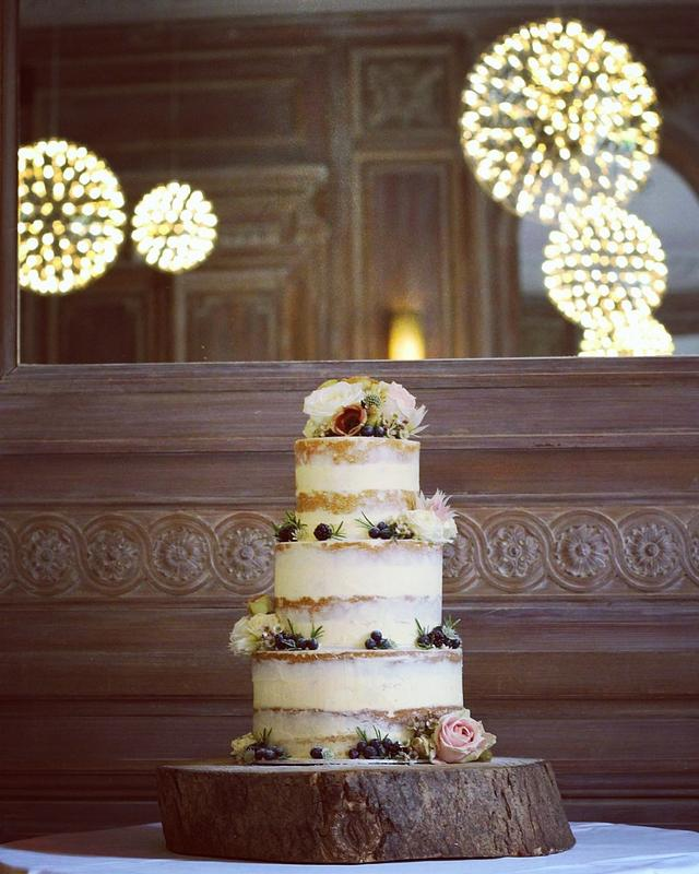 Semi naked wedding cake with blackberries and blueberries.