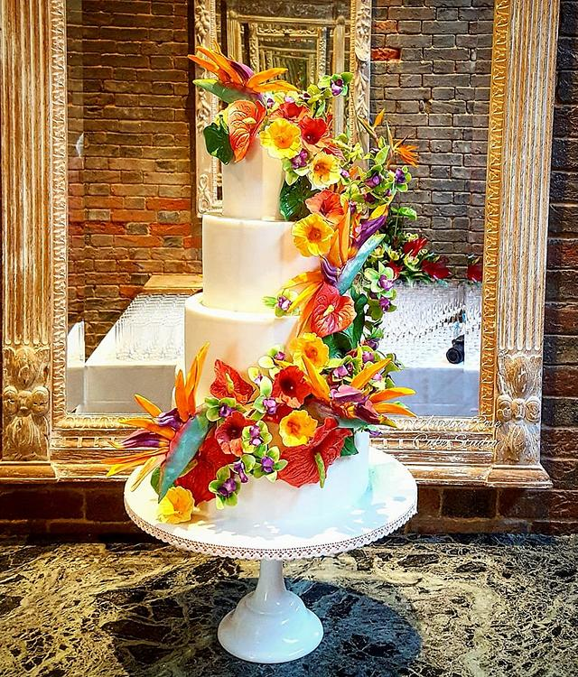 Tropical flower wedding cake with hidden beach scene