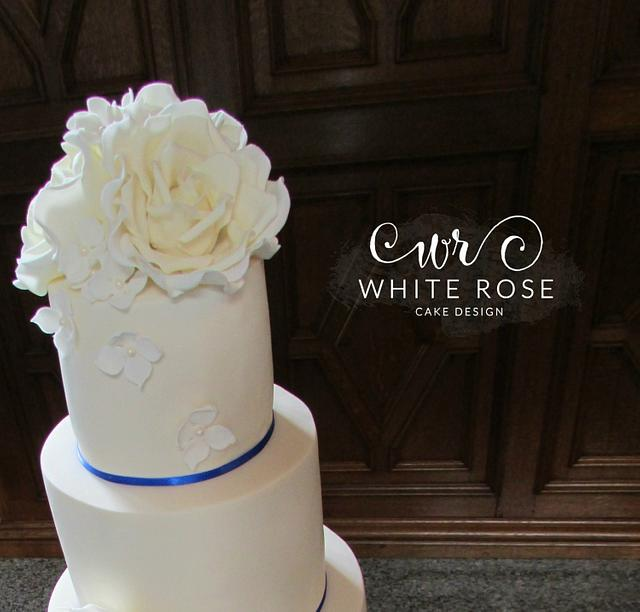 Five Tier Ivory Wedding Cake with Roses and Royal Blue Trim