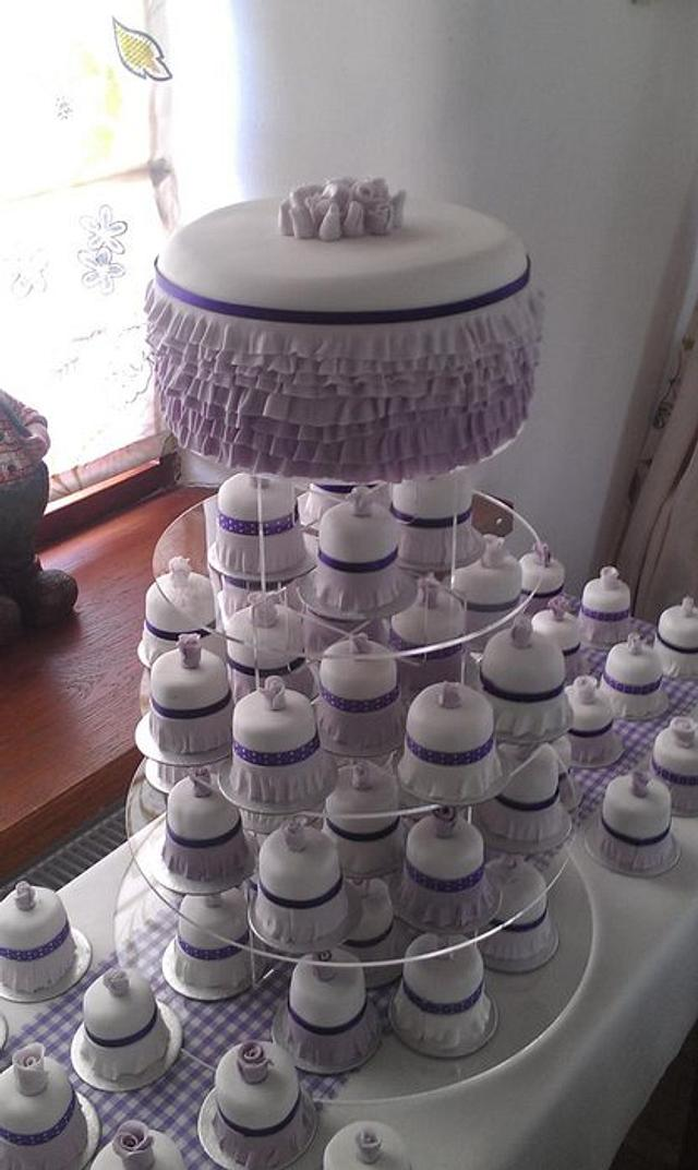 """Rainbow cake with lilac Ombre frills and 70 - 2"""" matching mini cakes"""