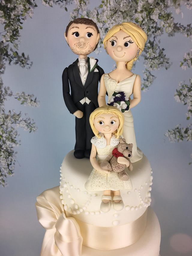 Ivory wedding cake with bride groom and flower girl sugar topper