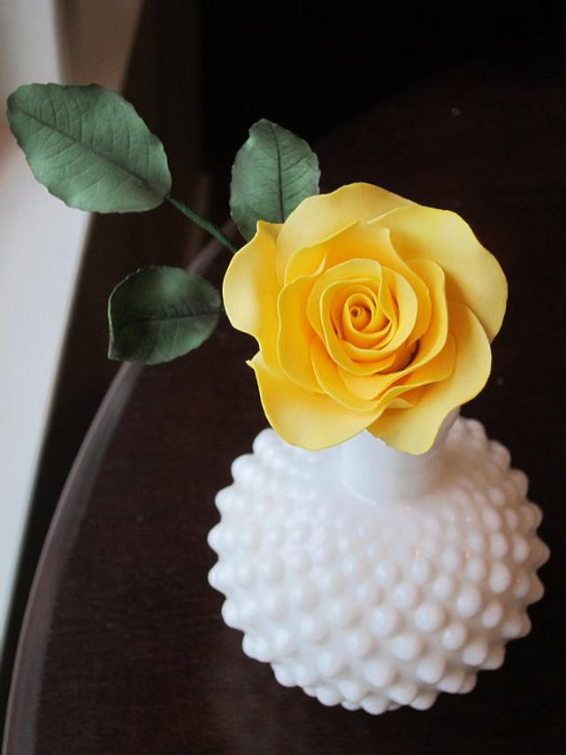 Yellow sugar rose and leaves in milk glass