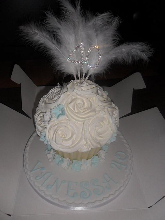 large giant white cupcake with feathers