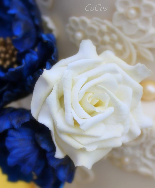 a royal blue and lace wedding cake and cupcakes