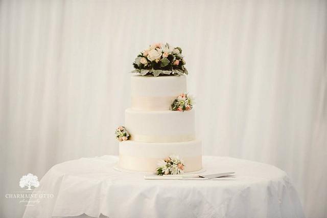 Simple three tier wedding cake with fresh flowers