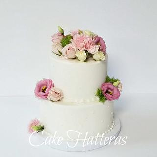 Buttercream iced wedding cake with fresh flowers