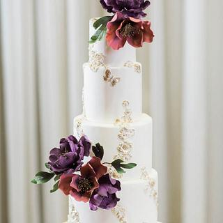Vintage bas-relief lace white and gold wedding cake with flowers.