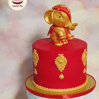 Gold and red cake with elephant topper