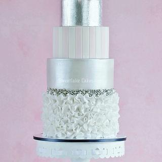 A double barrel cake with silver leaf and a peony