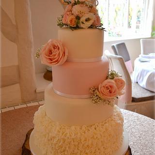 Blush pink roses and white ruffles wedding cake