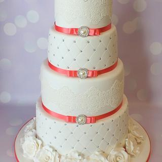 Four tier white and coral wedding cake