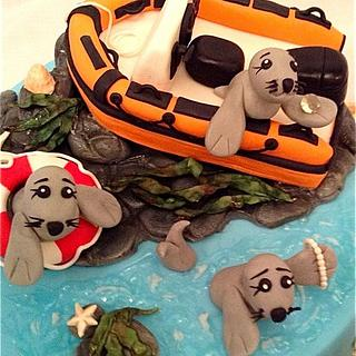 Seals, boat and puppies cake with jewellery cupcakes
