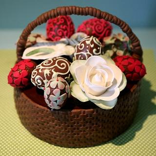 Easter basquet filled with decorated chocolate eggs and sugar flowers
