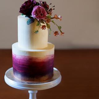 Dark ombré two tier cake with touches of gold and sugarpaste flowers.