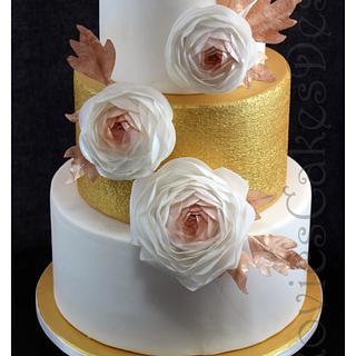 golden wedding display cake with ranunculuses