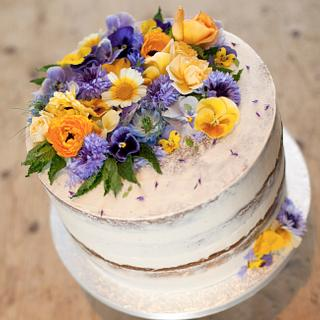 "Large single tier, semi-naked carrot cake with fresh ""edible grade"" organic flowers."