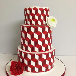 Modern red and white cake with geometric patterns.