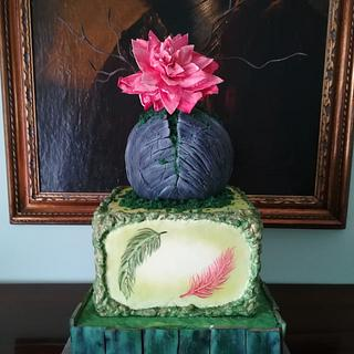 cake with green wood, painted feathers and rock with moss and wafer flower
