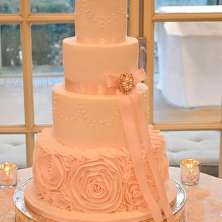 Pink ruffles and roses wedding cake