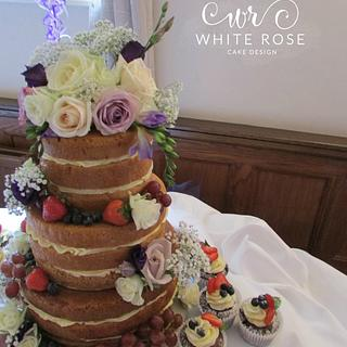Naked cake with fresh flowers and berries