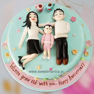 Anniversary theme designer cake with couple and newborn baby girl figurines