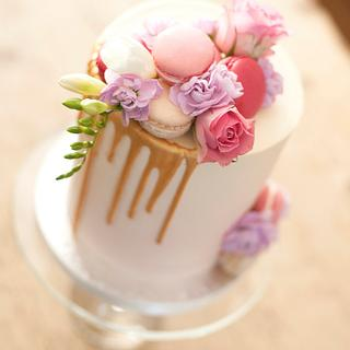 Delicate pink watercolour ombré birthday cake with gold drip, fresh flowers and macarons