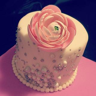 Small 6 inch cake with a sugar ranunculus flower