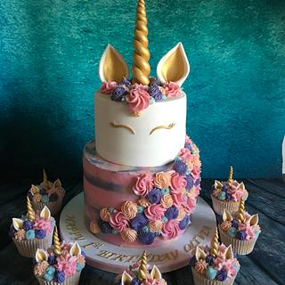 Tiered pastel unicorn cake and cupcakes