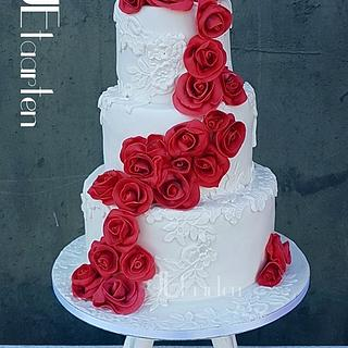 red roses on a white laced weddingcake