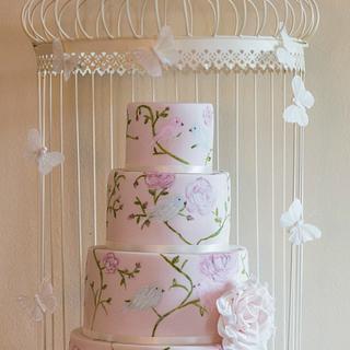 Pale pink hand painted love birds wedding cake