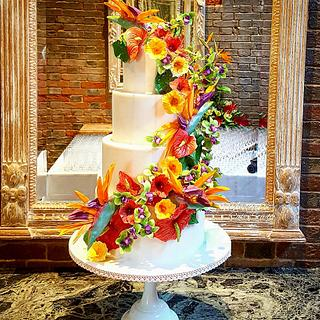 Tropical flower wedding cake with hidden beach scene