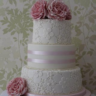 A three tier wedding cake with 2 embossed tiers and flowers