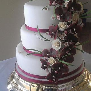 Tumbling burgundy orchid spray with cream roses, waxflower and grasses