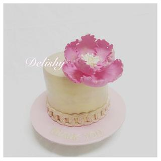 Gold cake with open poeny flower