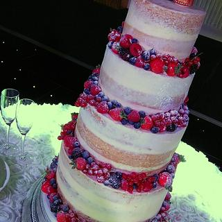 Semi-naked wedding cake with berries