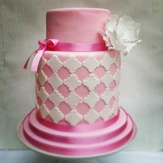 Pink double barrel cake with white quatrefoil design and sugar peony
