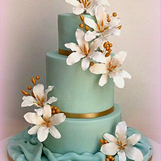 Wedding cake with sugar lilies and gold details