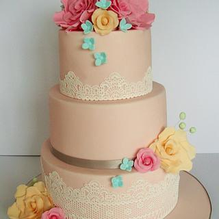 Peach wedding cake with roses and lace
