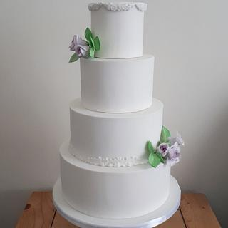 White wedding cake with lilac wired roses