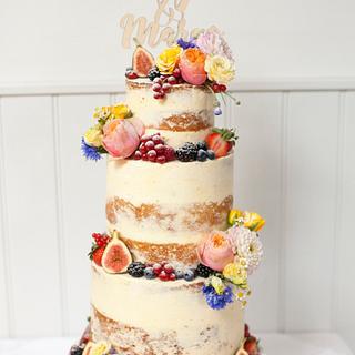 Semi-naked wedding cake with fruit and flowers