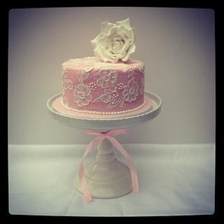 Pink cake with brush embroidery and a sugar rose.