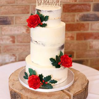 Semi-naked wedding cake with red sugarpaste roses and holly