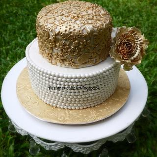 A simple vintage cake with gold lace work and sugar pearls .