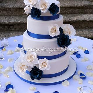 wedding cake with white roses and blue